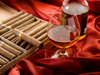 cuban cigar and bottle of  liquor  over red satin