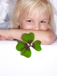 Cute little girl wishes luck with shamrock