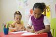 Jeunes enfants en classe de maternelle dessinant