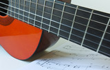 An Orange Classical Guitar and Sheet Music