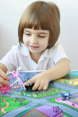 Little girl playing with cars and a traffic map