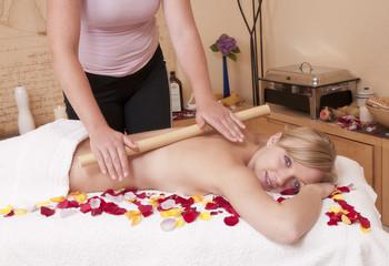 Bambusmassage - Wellnesmassage -  an einer hübschen, jungen Blo