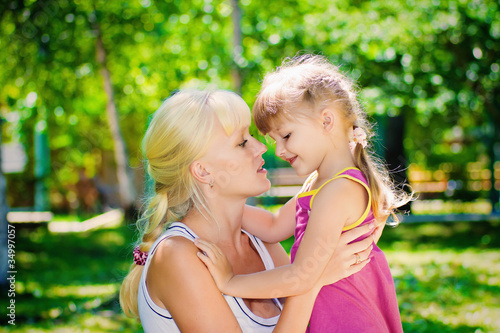 mother with a young daughter resting in a park