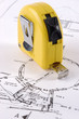 A yellow measuring tape on a architectural plan