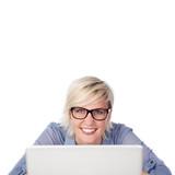 lächelnde frau mit brille am notebook