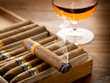 smoking cuban cigar and glass of  liquor on wood
