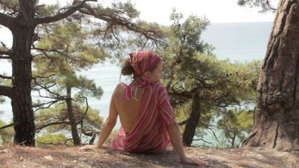 Young woman sits on a cliff against sea.