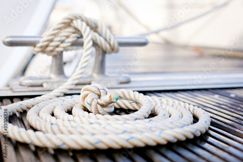 Mooring rope with a knotted end tied around a cleat. - 35006836