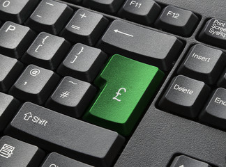 A Black Keyboard With Green Key Labelled £