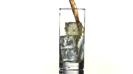 Cola pouring into glass with ice cubes in slow-motion