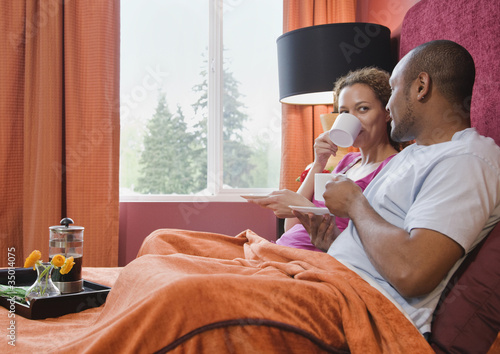African couple drinking coffee in bed