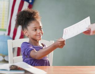 Mixed race girl receiving schoolwork from teacher