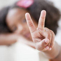 Mixed race girl making the peace symbol