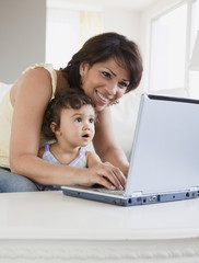 Hispanic mother and daughter looking at laptop