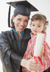 Hispanic mother graduate holding daughter and diploma