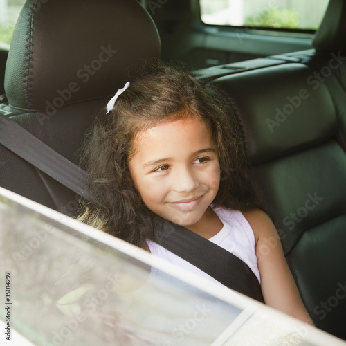 Hispanic girl in back seat of car