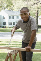 African boy sawing wood