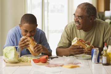 African grandfather and grandson eating lunch