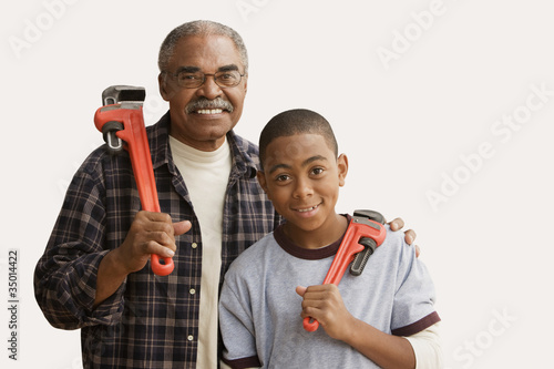 African grandfather and grandson holding wrenches