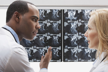 African doctor reviewing x-rays with co-worker
