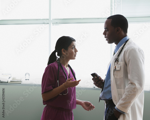 Doctor and nurse talking in hospital hallway