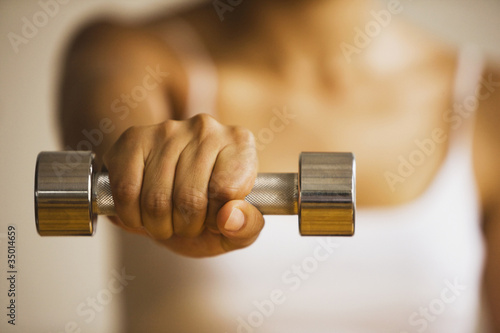Close up of Hispanic woman  holding hand weight