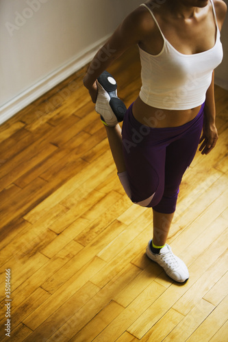 Hispanic woman stretching leg