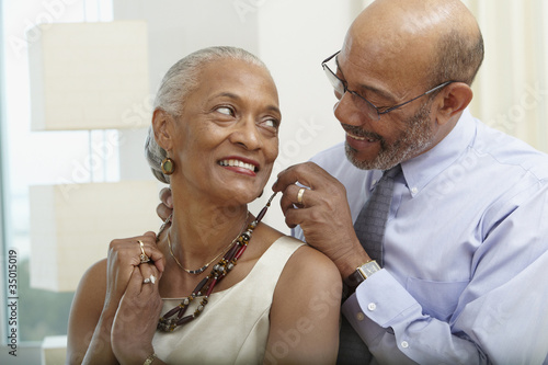 African man helping wife with necklace