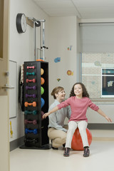 Physical therapist helping girl on exercise ball