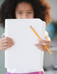 Hispanic girl holding out notebook