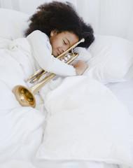 Hispanic girl sleeping with trumpet