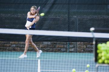 Hispanic woman practicing tennis