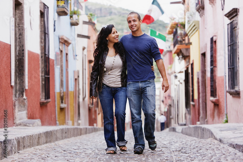 Hispanic couple walking on cobblestone street