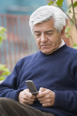 Senior Hispanic man text messaging on cell phone