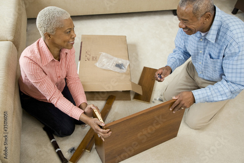 African couple assembling shelf