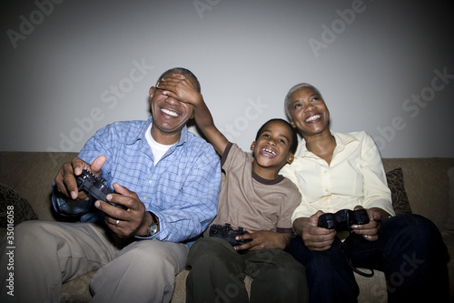 African grandparents playing video game with grandson