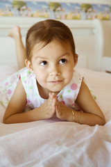 Hispanic girl praying on bed