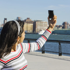 Hispanic woman taking self-portrait at the waterfront