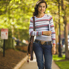 Hispanic woman walking along sidewalk
