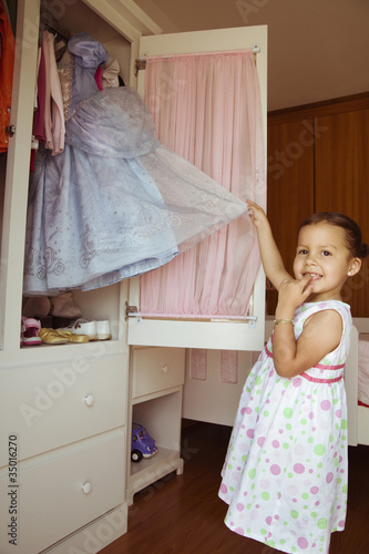 Hispanic girl taking costume from closet