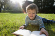 Mixed race boy reading book in grass
