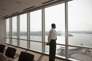 African American businessman looking out office window