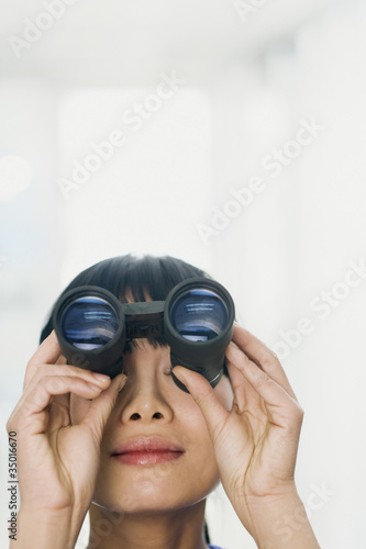 Chinese woman looking through binoculars