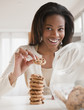 Mixed race woman taking cookie