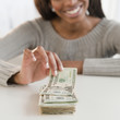 Mixed race woman taking money from stack