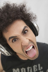Hispanic man in headphones grimacing