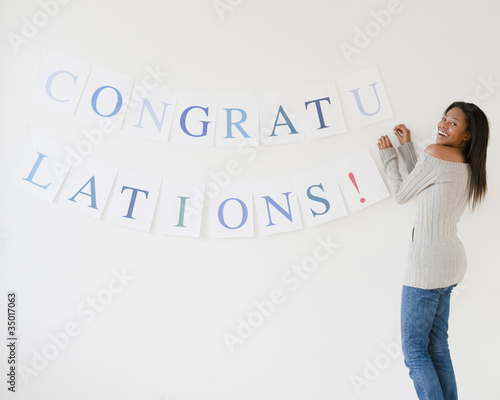 Mixed race woman putting up congratulations sign