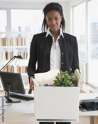 Fired mixed race businesswoman packing belongings