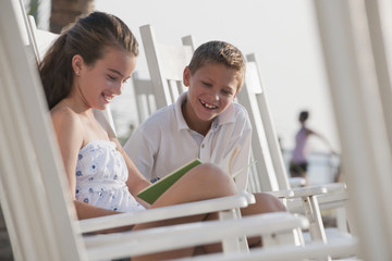 Caucasian boy and girl sitting in rocking chair