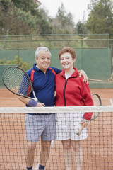 Senior Hispanic couple playing tennis